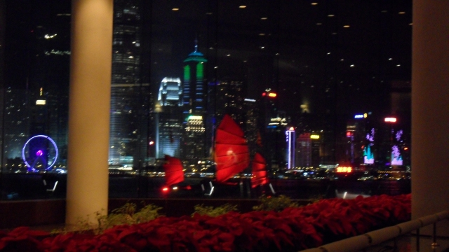 A Hong Kong junk sailing by - with its bright red sails illuminated at night it has a slightly ominous feel to it